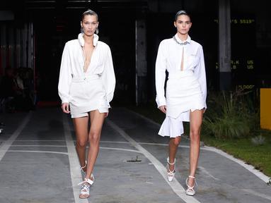 Model Bella Hadid dan Kendall Jenner berjalan di atas catwalk memakai busana Off White Spring/Summer 2019 selama Paris Fashion Week, Prancis (27/9). Kedua model tersebut tampil cantik membawakan koleksi rancangan Virgil Abloh. (AP Photo/Thibault Camus)