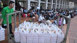 Petugas membagikan takjil jelang berbuka puasa pada hari kedua bulan Ramadan di Masjid Istiqlal, Jakarta, Minggu (28/5). Sebanyak 5000 kotak makanan dibagikan untuk berbuka pada gari Jumat - Minggu. (Liputan6.com/Helmi Afandi)