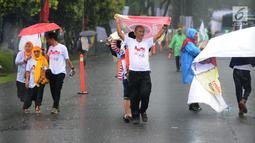 Pendukung calon presiden nomor urut 01 Joko Widodo diguyur hujan saat tiba di Sentul International Convention Center, Bogor, Jawa Barat, Minggu (24/2). Jokowi akan menyampaikan keberhasilan kebijakan pemerintah. (Liputan6.com/Herman Zakharia)