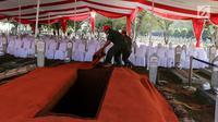 Pekerja menyiapkan karpet merah di makam Presiden ke-3 RI BJ Habibie di TMP Kalibata, Jakarta, Kamis (12/9/2019). Sejumlah petinggi dilaporkan bakal hadir menghadiri pemakaman Habibie. (Liputan6.com/Herman Zakharia)