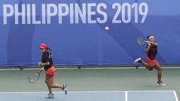 Ganda Indonesia, Priska Nugroho / Rifanty Kahfiani, saat melawan Peangtarin Plipuech / Tamarine Tanasugarn pada SEA Games 2019 di Kompleks Rizal Memorial, Kamis (5/12). Ganda Indonesia kalah 4-6, 7-6 dan 5-10. (Bola.com/M Iqbal Ichsan)