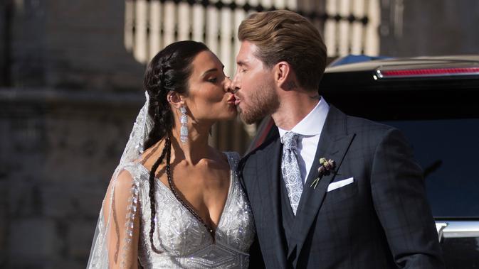 Bek Real Madrid, Sergio Ramos mencium istrinya Pilar Rubio setelah upacara pernikahan mereka di Sevilla, Spanyol (15/6/2019). Sergio Ramos dan Pilar Rubio telah memiliki tiga putra yaitu, Sergio, Marcos, dan Alejandro. (AP Photo/Antonio Pizarro)