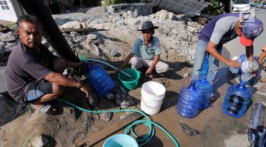 Warga antre memanfaatkan air bersih dari kebocoran pipa PDAM di Jalan Lagarutu, Palu Sulawesi Tengah, Rabu (3/10). Pasca gempa tsunami warga sekitar belum mendapatkan pasokan makanan dan air bersih. (Liputan6.com/Fery Pradolo)