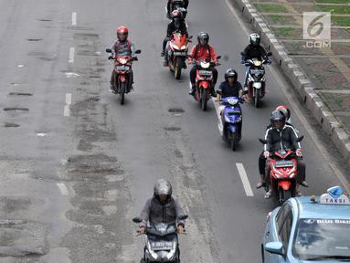 Kendaraan melintasi jalan berlubang di kawasan Gunung Sahari, Jakarta, Selasa (29/1). Sedikitnya terdapat 8 titik jalan rusak dan berlubang di sepanjang Jalan Gunung Sahari berdiameter hingga 10 cm dengan kedalaman 10 cm. (Merdeka.com/Iqbal S. Nugroho)