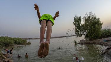 Seorang pemuda terjun ke Sungai Shatt Al-Arab di Kota Basra, Irak, Selasa (9/6/2020). Sungai yang memiliki panjang sekitar 200 Km ini menandai perbatasan antara Irak dan Iran. (Hussein FALEH/AFP)