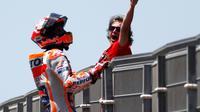 Pembalap Repsol Honda, Marc Marquez memanjat pagar lintasan setelah berhasil finis pertama pada balapan MotoGP Spanyol 2018 di Sirkuit Jerez, Minggu (6/5). Marquez mengukir waktu 41 menit 39,678 detik. (AP Photo/Miguel Morenatti)