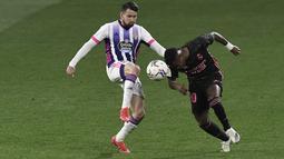 Pemain Real Valladolid, Luis Perez, berebut bola dengan pemain Real Madrid, Vinicius Junior, pada laga Liga Spanyol di Stadion Jose Zorrila, Minggu (21/2/2021). Real Madrid menang dengan skor 1-0. (AP/Alvaro Barrientos)