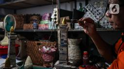 Sugito (68) menyelesaikan pembuatan miniatur Monas dari kertas koran bekas di Bank Sampah Tri Alam Lestari, Jakarta Selatan, Rabu (9/6/2021).  Barang kerajinan yang dibuat Sugito di antaranya tempat tisu, lampu hias, wadah buah, tatakan gelas, dan wadah air mineral. (Liputan6.com/Johan Tallo)