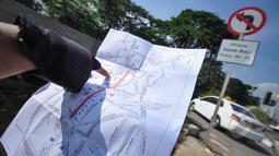 Petugas saat menujukan peta lokasi rambu larangan motor di Jalan Abdul Muis, Jakarta, Senin (6/4/2015). Pengendara sepeda motor diizinkan melintas mulai pukul 23.00 hingga 06.00 WIB. (Liputan6.com/Faizal Fanani)