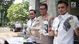 Kabid Humas Polda Metro Jaya Kombes Argo Yuwono (tengah) menunjukkan barang bukti kasus pengancaman pemenggalan terhadap Presiden Joko Widodo atau Jokowi di Mainhall PMJ, Jakarta, Senin (13/5/2019). Tersangka Hermawan Susanto sempat kabur sebelum akhirnya dibekuk polisi. (Liputan6.com/Faizal Fanani)