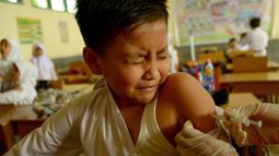 Siswa MIN Ulee Kareng menutup matanya saat mendapat vaksinasi anti virus difteri yang diberikan petugas Kesehatan di Banda Aceh, Aceh, Selasa (20/2). Dari catatan Dinkes, difteri kerap menyerang manusia kisaran usia 4 - 28 tahun. (CHAIDEER MAHYUDDIN/AFP)