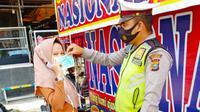 Personel Direktorat Lalu Lintas Polda Riau bagikan masker kepada penggendara saat Operasi Zebra. (Liputan6.com/M Syukur)