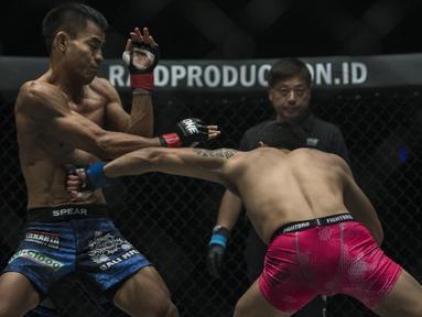 Atlet MMA Indonesia, Stefer Rahardian, terkena pukulan atlet MMA China, Peng Xue Wen, pada kelas strawweight di JCC Senayan, Jakarta, Sabtu (22/9/2018). Stefer Rahardian kalah dari Peng Xue Wen. (Bola.com/Vitalis Yogi Trisna)