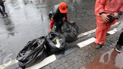Seorang petugas kebersihan DKI Jakarta membersihkan sampah usai aksi damai 2 Desember di kawasan Jalan MH Thamrin, Jakarta, Jumat (2/12). Aksi damai 2 Desember digelar sebagai lanjutan dari aksi 4 November 2016. (Liputan6.com/Ferbian Pradolo)