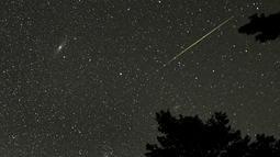 Sebuah meteor Perseid (kanan) terlihat di dekat Andromeda Galaxydi Taman Nasional Rocky Mountain, Colorado, Minggu (12/8). Peristiwa hujan meteor Perseid mengalami puncaknya akhir pekan ini pada 11-12 Agustus dan 12-13 Agustus. (AFP / STAN HONDA)