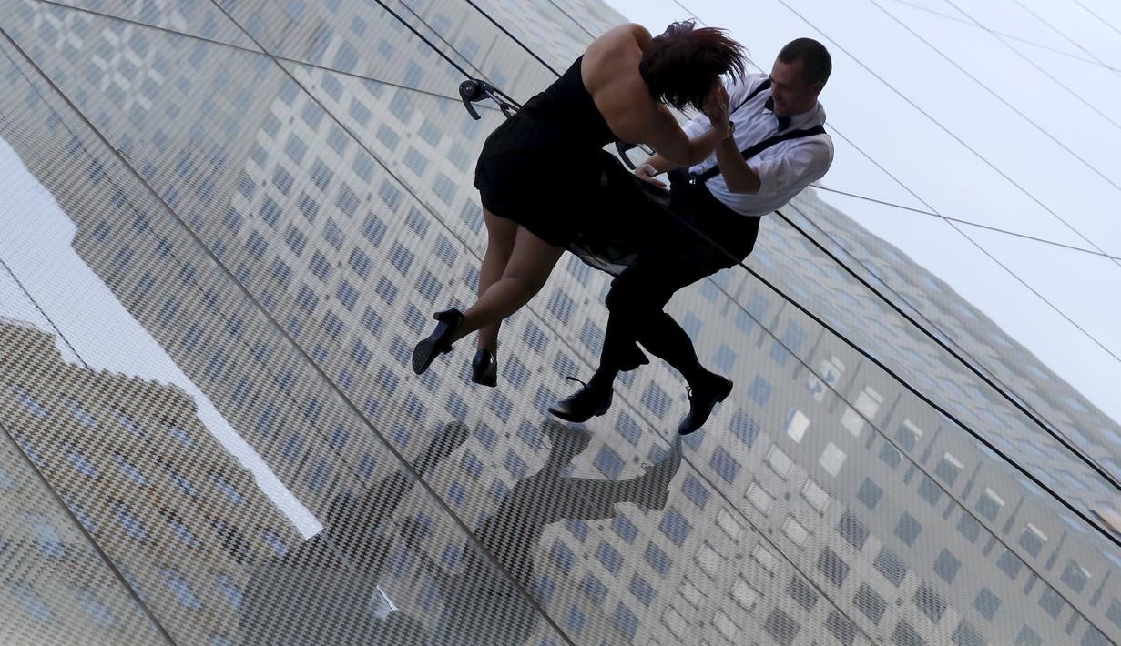 """Penari beraksi melakukan tarian di dinding bangunan gedung di Manhattan borough New York (19/4). Aksi nekat ini merupakan bagian dari pembukaan toko """"Hublot""""di Fifth Avenue, Manhattan. (REUTERS/Andrew Kelly)"""