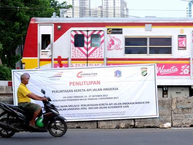 Warga melintas di depan spanduk sosialisasi penutupan perlintasan kereta di Jalan Angkasa, Jakarta, Minggu (15/10). Penutupan secara permanen perlintasan KA di Jalan Angkasa akan dilakukan pada 3 November mendatang. (Liputan6.com/Helmi Fithriansyah)