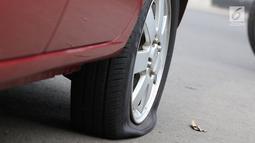 Ban mobil usai digembosi petugas akibat parkir sembarangan di kawasan Tebet, Jakarta, Kamis (28/3). Meskipun berulang kali ditertibakan, namun masih banyak pengendara yang nekat parkir sembarangan sehingga mengganggu arus lalu lintas. (Liputan6.com/Immanuel Antonius)