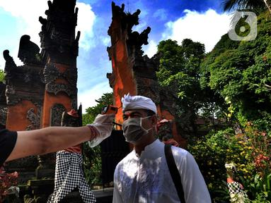 Petugas memeriksa suhu tubuh pengurus Pura Amerta Jati menjelang persiapan Hari Raya Nyepi Saka 1942 di Cinere, Depok, Selasa (24/3/2020). Rangkaian perayaan Nyepi di sejumlah pura hanya akan dilakukan oleh panitia dalam jumlah terbatas untuk mencegah penyebaran Covid-19. (merdeka.com/Arie Basuki)