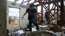 Dua orang pria mengumpulkan barang-barang yang masih tersisa dirumah mereka usai dilanda badai Harvey di Rockport, Texas (26/8). (Courtney Sacco/Corpus Christi Caller-Times via AP)
