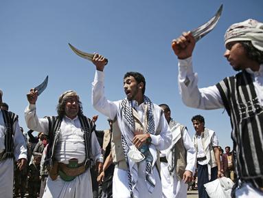 Tahanan Yaman (tengah) menampilkan tarian tradisional saat kedatangannya setelah dibebaskan koalisi pimpinan Arab Saudi di bandara di Sanaa, Yaman, Jumat (16/10/2020). Pihak yang bertikai di Yaman menyelesaikan pertukaran tahanan besar yang ditengahi PBB pada hari Jumat. (AP Photo/Hani Mohammed)