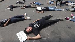 Aktivis berbaring saat menggelar aksi #BersihkanIndonesia di depan Istana Merdeka, Jakarta, Senin (19/8/2019). Aktivis menyerukan kebebasan hakiki dari kerusakan lingkungan dengan meninggalkan sumber energi fosil dari batu bara kotor beralih ke energi bersih terbarukan. (Liputa6.com/Angga Yuniar)