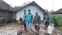 Nampak warga dan aparat TNI tengah membersihkan lumpur akibat sapuan banjir bandang (Liputan6.com/Jayadi Supriadin)