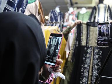 Pedagang menjualkan pakaian melalui melalui aplikasi online di Pasar Tanah Abang, Jakarta, Rabu (1/7/2020). Pedagang di Pasar Tanah Abang mulai menjual barang secara daring untuk menambah penjualan dan mengantisipasi turunnya jumlah pembeli di masa PSBB Transisi ini. (Liputan6.com/Faizal Fanani)