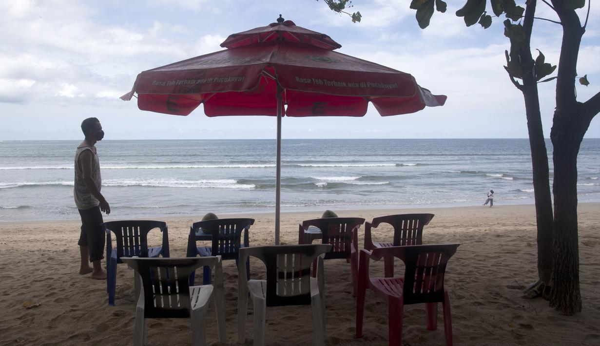 Seorang pedagang menata kursi saat menunggu pelanggan di Pantai Kuta, Bali, Kamis (14/10/2021). Pemerintah mulai membuka penerbangan internasional ke Bali bagi 19 wisatawan mancanegara mulai hari ini. (AP Photo/Firdia Lisnawati)