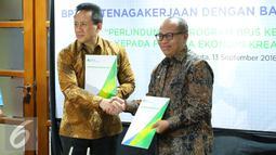 Dirut BPJS Ketenagakerjaan Agus Susanto (kanan) berjabat tangan dengan Kepala Badan Ekonomi Kreatif Triawan Munaf usai menandatangani nota kesepahaman di Jakarta, Rabu (13/9). (Liputan6.com/Angga Yuniar)