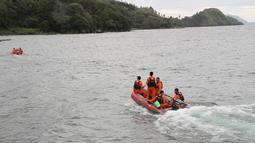 Tim penyelamat mencari korban hilang KM Sinar Bangun yang tenggelam di Danau Toba, Sumatera Utara, Selasa (19/6). Diduga, penumpang KM Sinar Bangun saat tenggelam berjumlah 80 orang. (AFP Photo/Lazuardy Fahmi)