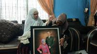Istri Serma Rama, prajurit TNI gugur di Kongo, dan orangtuanya di rumah duka Jalan Garuda Sakti Kabupaten Kampar. (Liputan6.com/M Syukur)
