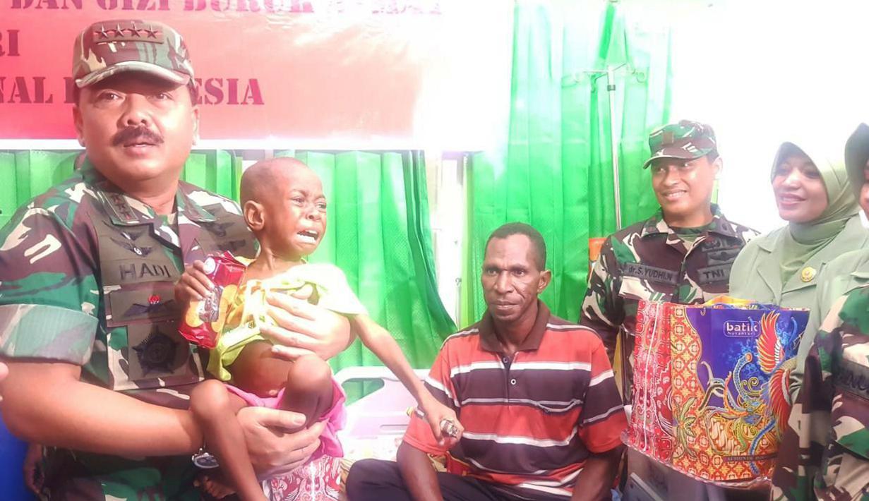 Panglima TNI Marsekal Hadi Tjahjanto menggendong seorang anak Suku Asmat yang menderita gizi buruk, Kamis (1/2). Satgaskes TNI KLB sudah melaksanakan vaksinasi terhadap 13.336 anak-anak di 224 kampung Kabupaten Asmat. (Liputan6.com/Pool/Puspen TNI)