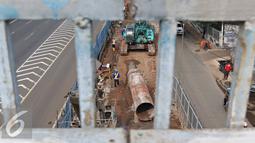Pekerja menyelesaikan pembangunan proyek MRT di Jalan R. A Kartini, Lebak Bulus, Jakarta Selatan, Senin (4/4). Proyek yang memakan separuh badan jalan tersebut menyebabkan kemacetan, terutama saat jam sibuk. (Liputan6.com/Immanuel Antonius)