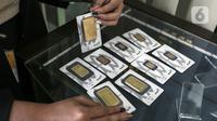 Pramuniaga menunjukkan emas batangan PT Aneka Tambang (Antam) Tbk di sebuah gerai emas, Jakarta, Senin (18/1/2021). Harga emas Antam kembali susut Rp 4.000 per gram di awal pekan. (Liputan6.com/Johan Tallo)