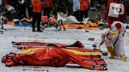 Petugas menyemprotkan disinfektan ke kantong jenazah korban pesawat Sriwijaya Air SJ-182 yang jatuh di perairan Pulau Seribu, di Dermaga JICT, Jakarta, Selasa (12/1/2021). Petugas gabungan juga menyerahkan satu kantong perlengkapan pribadi korban. (Liputan6.com/Johan Tallo)