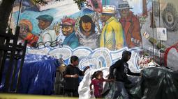 Orang berjalan melewati mural di Skid Row, Los Angeles, California, Kamis (1/10/2015). Kota Los Angeles menetapkan status darurat terkait makin rumitnya persoalan kaum tunawisma di sana. (REUTERS/Lucy Nicholson)