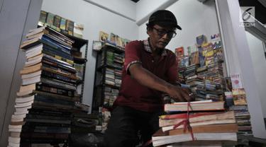 Pedagang  merapikan buku di salah satu kios Wisata Buku, Pasar Kenari, Jakarta, Selasa (20/8/2019). Sentra buku ini merupakan pindahan dari kios di Kwitang dan Pasar Senen. (merdeka.com/Iqbal S. Nugroho)