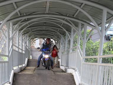 Pemotor melintasi JPO untuk menyeberangi rel kereta di kawasan Pasar Minggu, Jakarta, Selasa (6/9). Selain melanggar aturan, perilaku buruk pemotor tersebut juga membahayakan keselamatan diri sendiri serta pejalan kaki. (Liputan6.com/Immanuel Antonius)