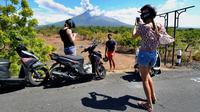 Sejumlah turis mengabadikan pemandangan erupsi Gunung Agung di Kabupaten Karangasem, Bali, Jumat (6/7). Erupsi Gunung Agung mengundang banyak perhatian warga dan wisatawan. (AFP FOTO / Sonny Tumbelaka)