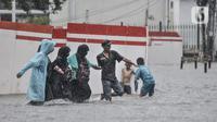 Warga membantu pengguna kereta menerobos banjir di Jalan Abdullah Syafei, Tebet, Jakarta, Kamis (18/2/2021). Hujan deras yang mengguyur sejak pagi menyebabkan aliran Kali Tebet meluap hingga merendam Jalan Abdullah Syafei dengan ketinggian mencapai sepaha orang dewasa. (merdeka.com/Iqbal S Nugroho)