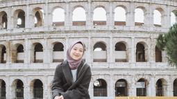 Berlibur ke Colosseum di Roma, Italia, Gita mengenakan coat berwarna abu-abu yang dipadukan dengan hijab segiempat berwarna taro, celana jeans, dan sneakers. (Liputan6.com/IG/@gitasav)