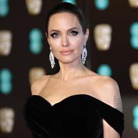 Aktris Angelina Jolie berpose saat tiba di BAFTA Awards 2018 di London, Inggris (18/2). Angelina tampil cantik dan seksi mengenakan gaun berwarna hitam dengan pundak terbuka. (Photo by Vianney Le Caer/Invision/AP)