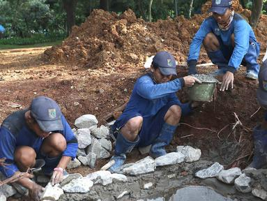 Petugas menyelesaikan pembuatan sumur resapan di kawasan Monas, Jakarta, Selasa (26/2). Pemkot Jakarta Pusat akan membangun 1.000 sumur resapan yang tersebar di berbagai lokasi untuk menampung air hujan. (Liputan6.com/Immanuel Antonius)