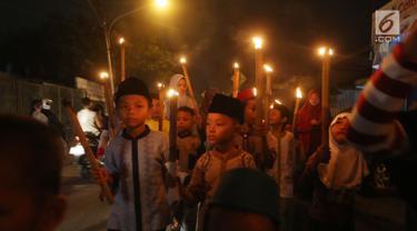 Sejumlah anak berpawai sambil membawa obor di Jalan Tengah, Batu Ampar, Jakarta Timur, Sabtu (24/6). Kegiatan tersebut dalam rangka menyambut Idul Fitri 1 Syawal 1438 Hijriyah. (Liputan6.com/Angga Yuniar)