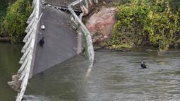 Tim penyelamat menyelam di  sungai Tarm, dekat jembatan gantung yang ambruk di Prancis, Selasa (18/11/2019). Satu mobil dan satu truk dan kemungkinan sebuah kendaraan lainnya yang sedang melintasi jembatan itu langsung hanyut ke sungai. (ERIC CABANIS/AFP)