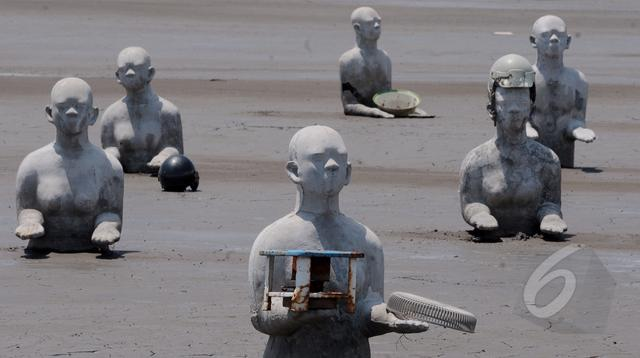Seniman membuatkan patung bagi warga korban kepada pemerintah di wisata lumpur lapindo, Sidoarjo, Senin (30/03/2015). Sudah 9 tahun kawasan ini terendam oleh lumpur, tidak terhitung kerugian yang diderita warga sekitar. (Liputan6.com/Andrian M Tunay)