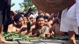 Sejumlah pria Bali menonton Perang Pandan di Bali (8/6). Perang Pandan merupakan salah satu tradisi yang dilakukan untuk menghormati dewa Indra atau Dewa perang. (AP/Firdia Lisnawati)