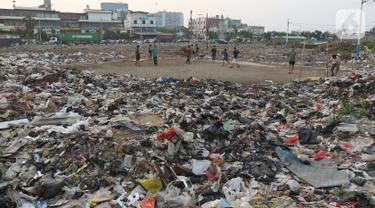 Sejumlah warga bermain sepak bola di antara tumpukan sampah di kawasan Penjaringan, Jakarta, Jumat (1/11/2019). Minimnya lahan bermain di Jakarta membuat warga bermain sepak bola di sekitar tumpukan sampah. (Liputan6.com/Herman Zakharia)
