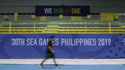 Seseorang melintas tribun venue bulutangkis SEA Games 2019 di Muntinlupa Sports Center, Manila, Sabtu (23/11). Cabang bulutangkis akan mulai bertanding pada Minggu (1/12). (Bola.com/M Iqbal Ichsan)